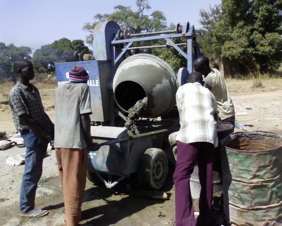 Construction d'un radier:des ouvriers au niveau d'une bétonnière